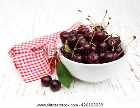 Bowl with cherries on a old wooden background