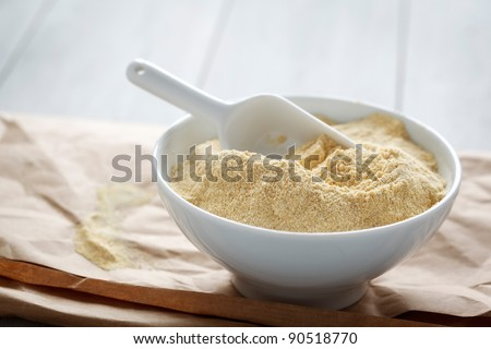 Bowl with chickpea flour on a paper. - stock photo