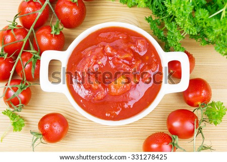 Bowl with chopped tomatoes and parsley on wood - stock photo