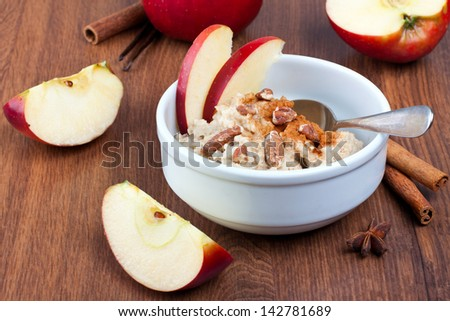 Bowl with cinnamon and nuts oatmeal with  apples on wooden background