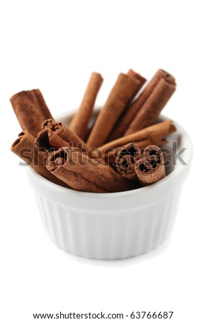 Bowl with cinnamon sticks isolated on white background. Shallow dof - stock photo