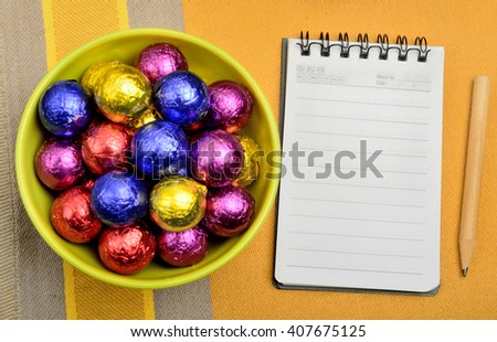 Bowl with colorful chocolate and empty notebook on table - stock photo