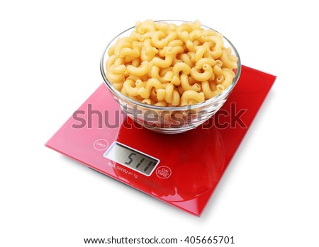 Bowl with dry pasta on digital kitchen scales, isolated on white - stock photo