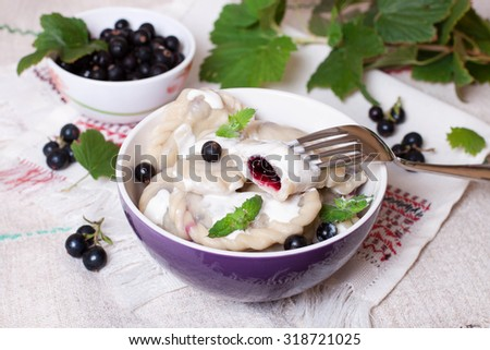 Bowl with dumplings with black currant