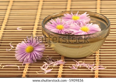 Bowl with flowers on a wooden napkin