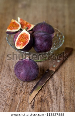 bowl with fresh figs and old knife on rustic wooden table - stock photo