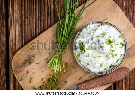 Bowl with Herb Curd (detailed close-up shot) on wooden background