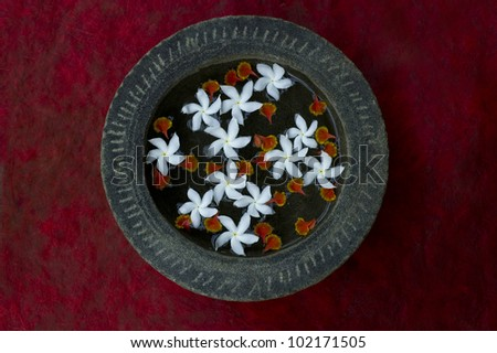 Bowl with jasmine flowers in water and river stone - stock photo