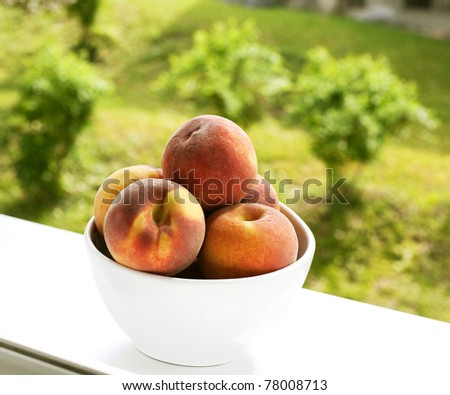 bowl with juicy peaches on window-sill