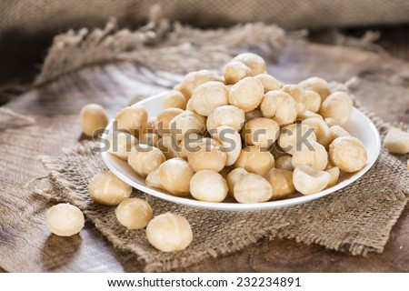 Bowl with Macadamia nuts on dark rustic wooden background - stock photo