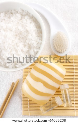 Bowl with natural salt of Dead Sea, bar of soap, brush and ampules with serum on white towel. - stock photo