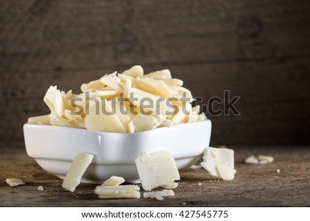 Bowl with parmesan cheese flakes on rustic table