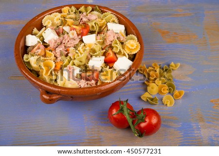 Bowl with pasta salad and some of its ingredients - stock photo