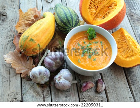 Bowl with pumpkin cream soup with parsley and whole pumpkin - stock photo
