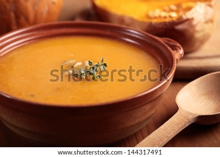 Bowl with pumpkin soup and and baked butternut squash - stock photo