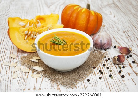 bowl with pumpkin soup on a wooden background - stock photo