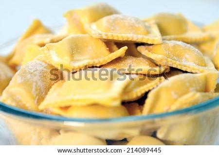 Bowl with ravioli on blue background - stock photo