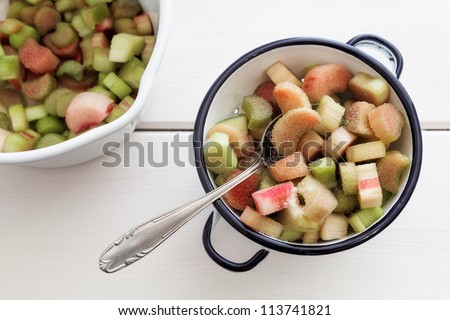 Bowl with rhubarb compote on a white wooden board.