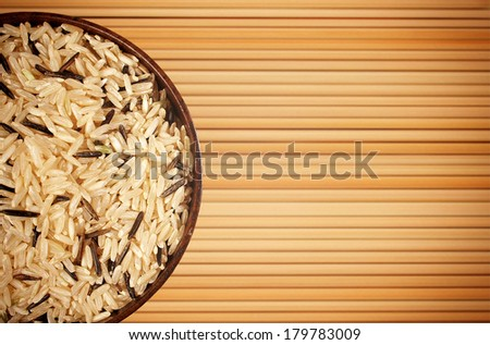 bowl with rice on the mat  background - stock photo