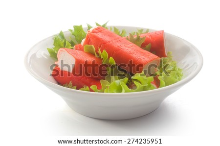 Bowl with some red crab sticks with fresh green lettuce - stock photo