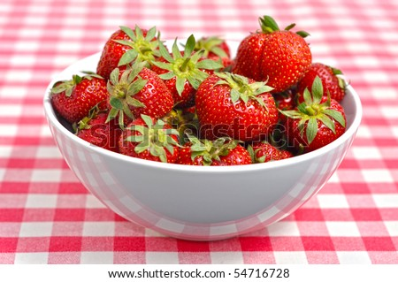 Bowl with strawberries on a chequered patterned table-cover - stock photo
