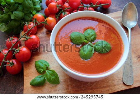 Bowl with tasty tomato soup on wooden board - stock photo