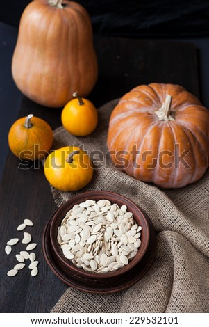 bowl with toasted pumpkin seeds, pumpkins