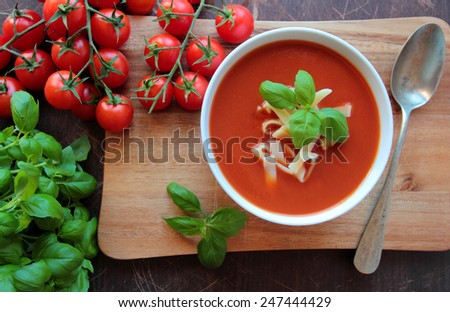 Bowl with tomato cream soup with homemade macaroni - stock photo