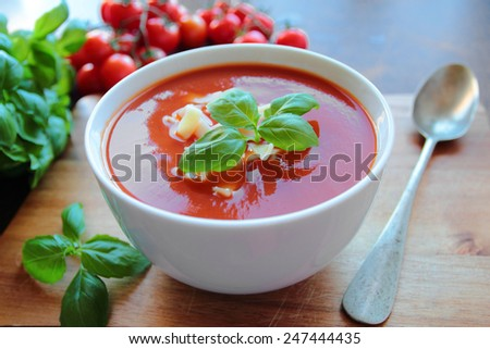 Bowl with tomato soup with macaroni and basil