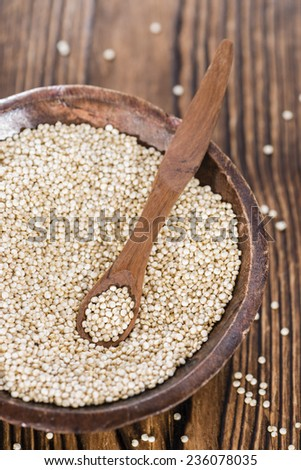 Bowl with uncooked Quinoa seeds (close-up shot) on wooden background