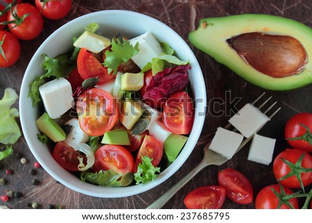 Bowl with vegetable salad with tomatoes avocado lettuce and feta cheese - stock photo
