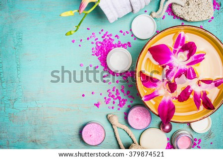 Bowl with water and pink orchid flowers  with wellness and spa setting on turquoise blue background, top view, close up. - stock photo