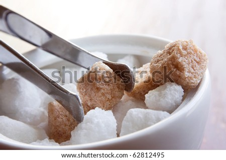 Bowl with white and brown sugar cubes and tongs - stock photo