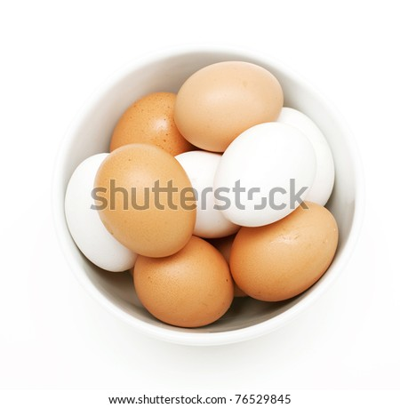 bowl with white and yellow eggs on white background - stock photo