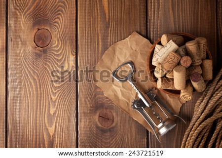 Bowl with wine corks and corkscrew. View from above over rustic wooden table background with copy space