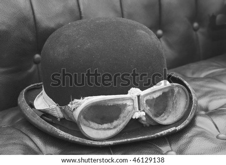 Bowler hat and goggles in veteran car - stock photo