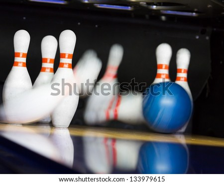Bowling ball hitting motion blurred pins - stock photo
