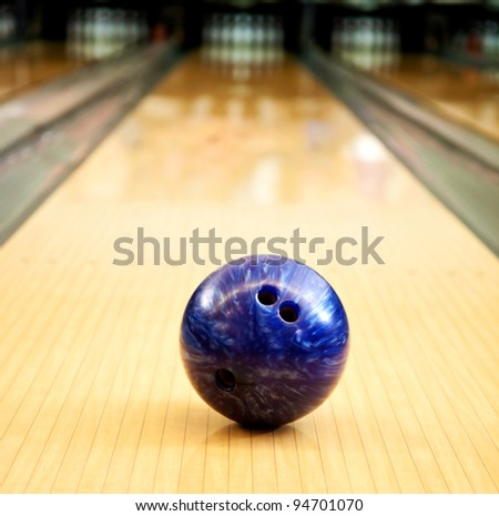 Bowling ball in an alley heading towards the pins