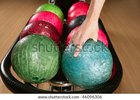 Bowling ball in player man hand in colorful rows - stock photo
