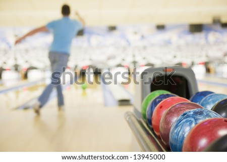 Bowling ball machine with man bowling in the background