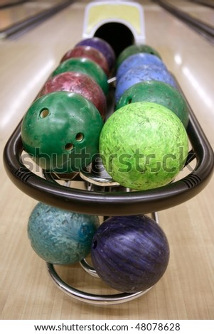 Bowling balls perspective in game center wooden floor - stock photo