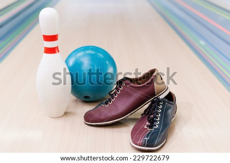 Bowling equipment . Close-up of bowling shoes, blue ball and pin lying on bowling alley   - stock photo