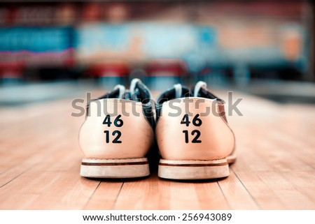 Bowling footwear. Close up of bowling shoes lying on bowling alley - stock photo