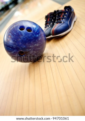 Bowling kit with shoes and ball on the alley - stock photo