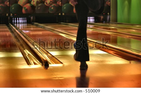 Bowling lanes - shallow DOF, focus is set on leg/ bowl behind - stock photo
