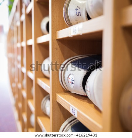 Bowling shoes in a shoe cabinet sorted by size - stock photo