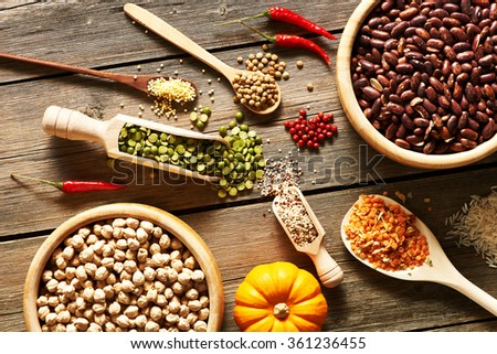 Bowls and spoons of various legumes on wooden background - stock photo