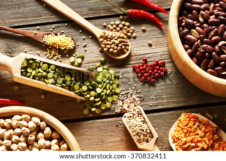 Bowls and spoons of various legumes on wooden background