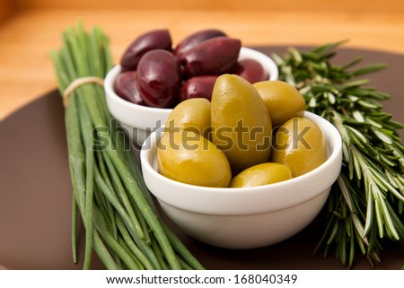 Bowls filled with pickled olives on clay plate. With a sprig of rosemary and chives. - stock photo