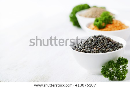 Bowls of assorted dried lentils with red lentils, black beluga lentils and mountain lentils over white - stock photo